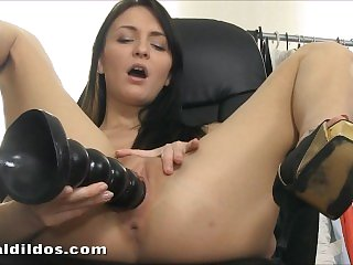 Hot young brunette babe fucking her pussy with a big black rippled dildo
